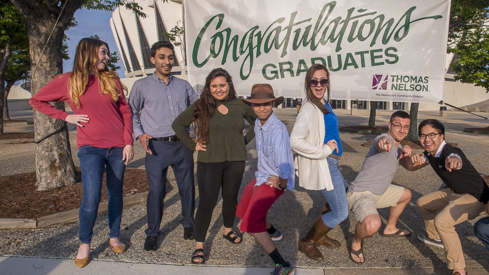 Graduates in front of sign Congratulating Grads at Coliseum
