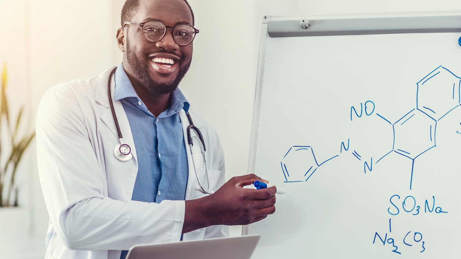Smiling medical professional pointing toward chemical formula