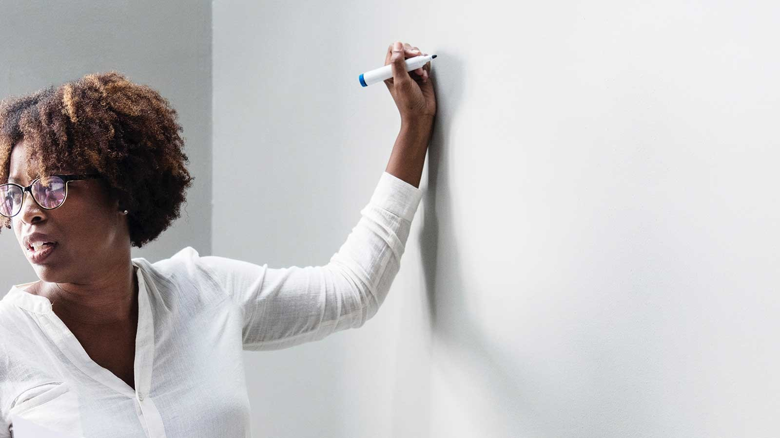 Female teacher standing in front of a white board