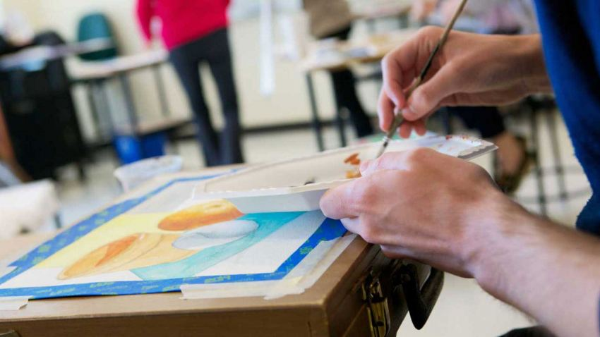 Photo of a watercolor still-life painting, painters palette and student holding a paintbrush